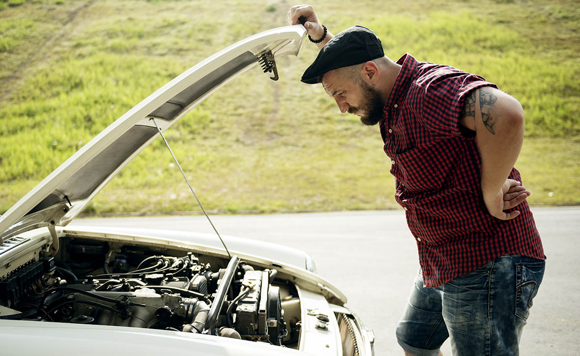 Mann steht vor einem Auto mit Motorschaden
